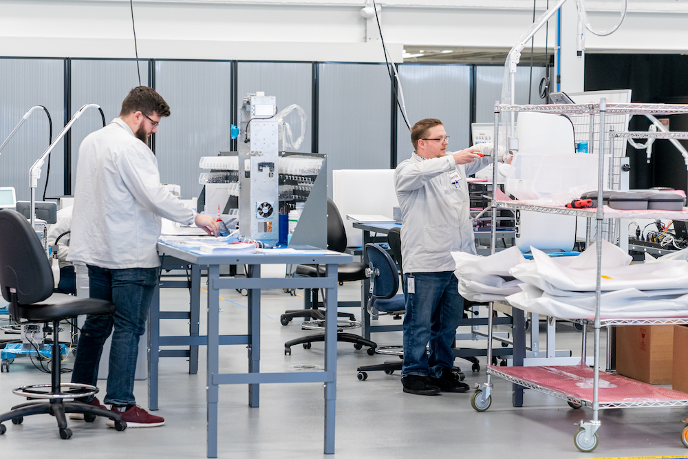 Two medical device assembly associates working on a manufacturing floor.